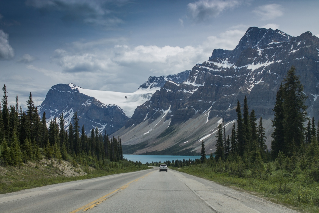 car driving along the Trans-Canada highway with views of the rocky mountains. Places to visit in Canada.