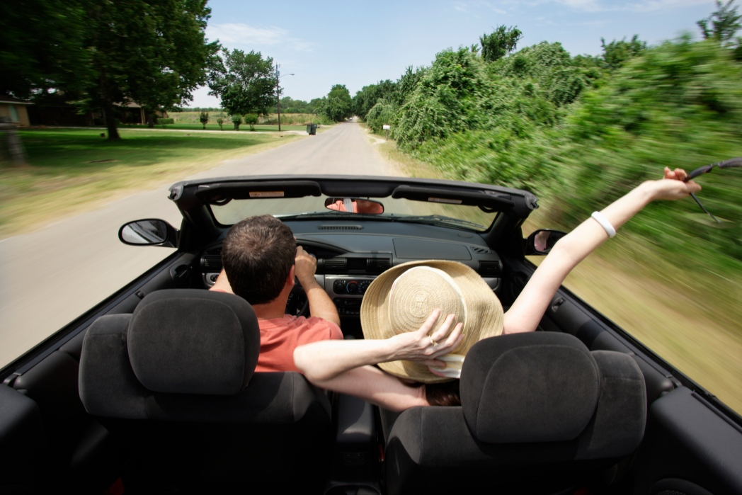 Image of two people in a convertible driving alone a countryside road. Tips to Help You Get the Best Car Rental Deals / Skyscanner Canada