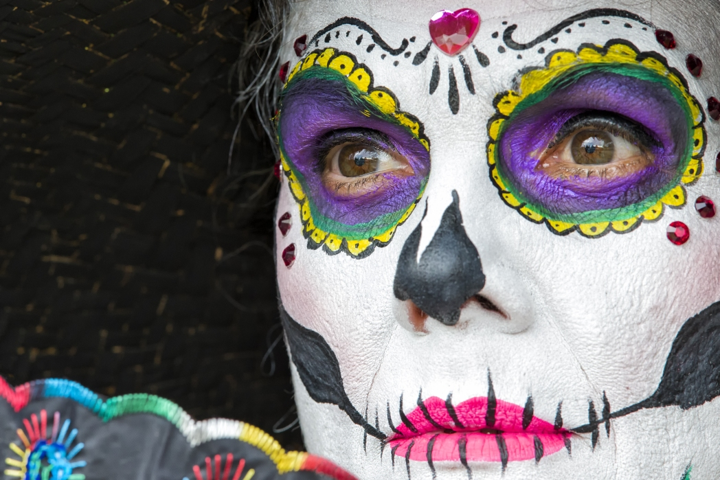 Closeup of a woman's face covered in Day of the Dead makeup, which looks like a colourful skeleton skull.  Day of the Dead in Mexico / Skyscanner Canada